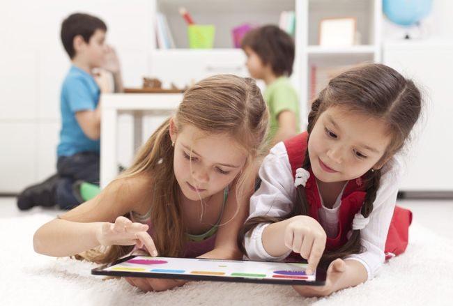 Две девочки играют на планшете