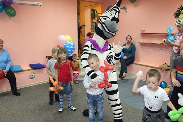 Дети веселятся с зеброй