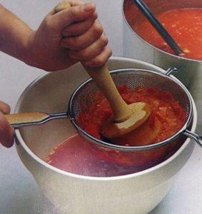 Процеживание варенных помидоров через сито
